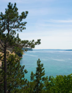 The turquoise coastline of Pictured Rocks, MI is framed by trees.