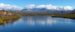 A panoramic shot of a lake in Arizona. Clouds roll over hills in the distance.