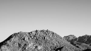A black and white image of foothills blemished by boulders.
