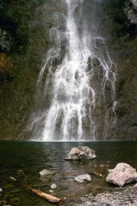 A shower of water gracefully drifts down a rock face to meet a small reservoir.