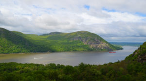 Two boats crossing the Hudson River are dwarfed by foothills.