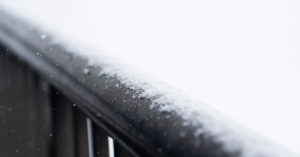 A macro shot of a hand rail dusted with recent snow fall. Snow particles fall out of focus.