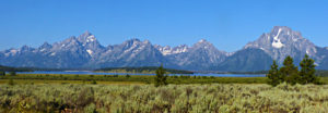 A panoramic image of the Teton Mountain range with a lake before it.